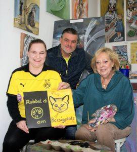 """Stephanie Schneider (links) hat das Bild """"Rubbeldikatz am Borsigplatz"""" ersteigert. Mit ihr freuen sich Bernd Uhlenbruck (IN-Stadtmagazine) und die Künstlerin Dagmar Schnecke-Bend (Foto: Rüdiger Beck)."""