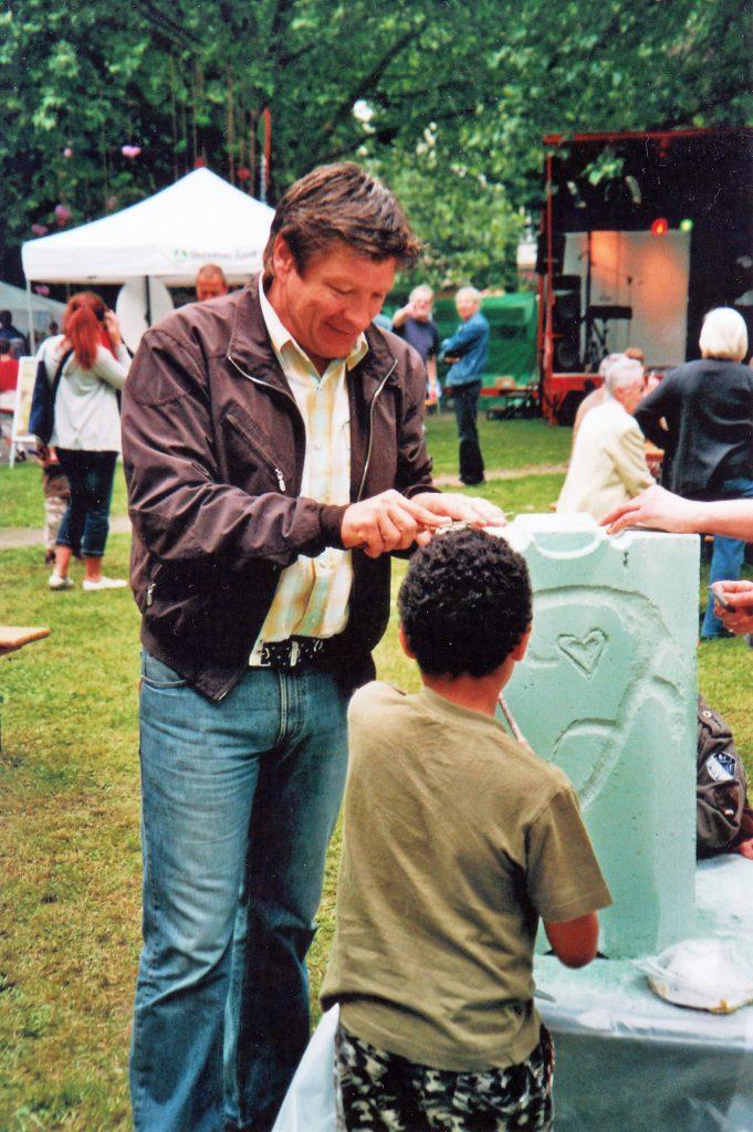 """Auch vielen bekannten Persönlichkeiten hat Dagmar Schnecke-Bend die Bearbeitung eines Gasbetonsteins erläutert und zum Mitmachen aufgefordert. Das Foto zeigt Bruno """"Günna"""" Knust bei der Eröffnung des Familienfestes """"Kreuzviertel Pur"""" im Jahr 2010."""