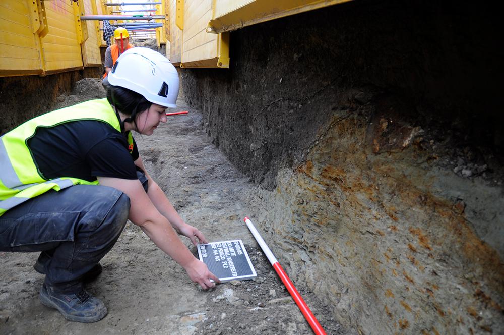 Deutlich erkennbar, die dunkelgrauen Schichten der Grabenverfüllung im Profil und im Planum des Leitungsgrabens. Die Sohle des Wassergrabens wurde bei den Arbeiten nicht erreicht. Denn ausgegraben wird immer nur so viel wie unbedingt durch die Baumaßnahme erforderlich. (Bildrechte: Stadt Dortmund / LQ-Archäologie)