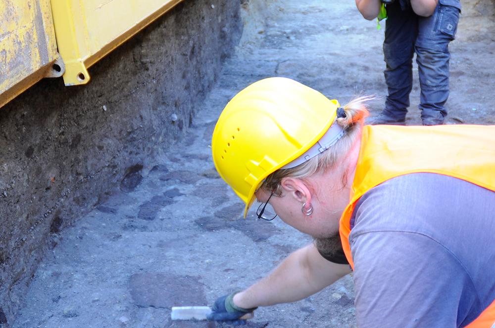 """Damals Abfall, heute wertvolle Hilfe. Was aussieht wie braune unförmige Flecken in der Grabenverfüllung ist in Wahrheit Holz, das beim Verfüllen mit in den Graben gelangt war. Als Füllmaterial hatte man alles verwendet was in der Nähe verfügbar war und nicht mehr genutzt wurde. Heute kann man mit der sogenannten """"14C-Methode"""" das Alter des Holzes bestimmen, um so weitere Anhaltspunkte zum Alter des Grabens zu erhalten. (Bildrechte: Stadt Dortmund / LQ-Archäologie)"""