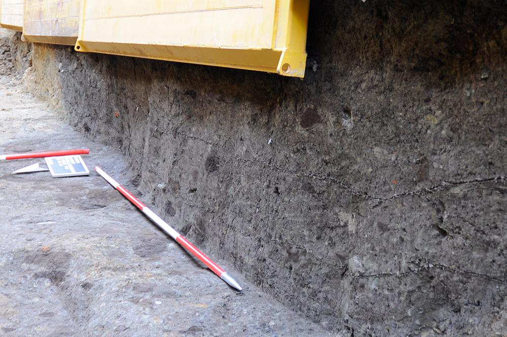 Der ehemals wasserführende Graben hatte ein v-förmiges Profil. Um die notwendige Tiefe zu erreichen, hatte man tief in den natürlichen Lehmboden gegraben. Dank der dunkelgrauen Grabenverfüllung lässt sich der ehemalige Graben hervorragend von dem gelb-grauen Lehmboden abgrenzen. (Bildrechte: Stadt Dortmund / LQ-Archäologie)