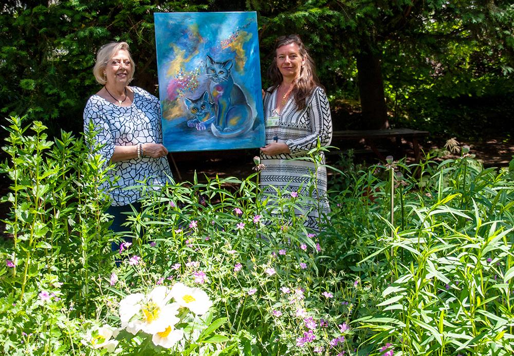 """Die Künstlerin Dagmar Schnecke-Bend (links) hat das Bild """"Glückskatzen"""" an die Kunsttherapeutin Michaela Killus übergeben. Foto: Rüdiger Beck"""